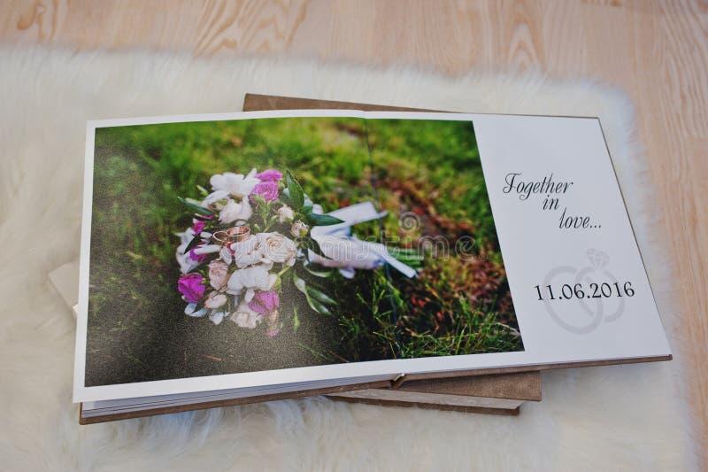 Páginas del photobook de la boda o del álbum de la boda en la alfombra en de madera imagen de archivo libre de regalías