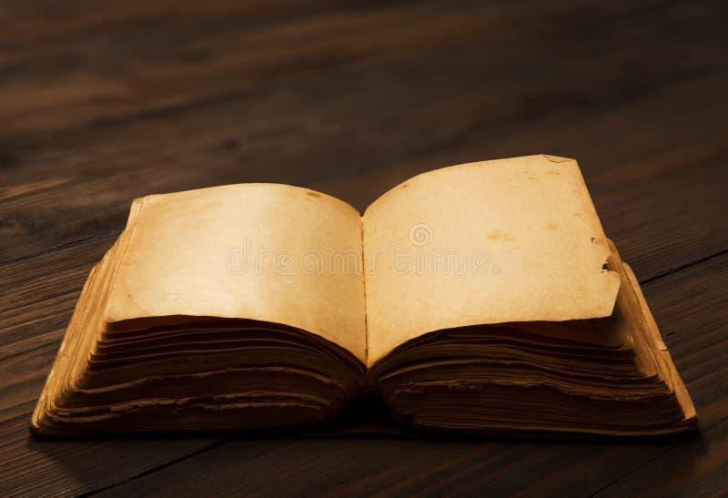 Páginas vazias abertas de livro velho, papel vazio na tabela de madeira imagens de stock