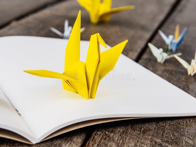 Pájaro amarillo de la papiroflexia en el Libro Blanco fotos de archivo libres de regalías