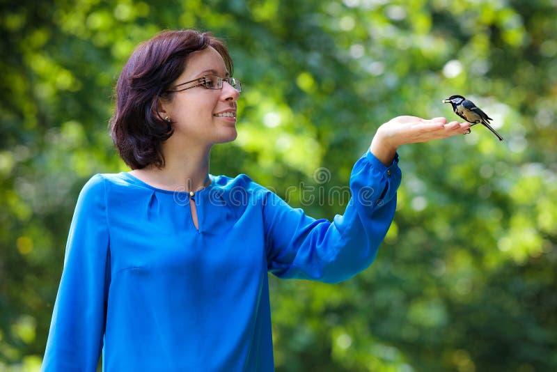 Pájaro de alimentación del paro carbonero de la mujer joven imágenes de archivo libres de regalías