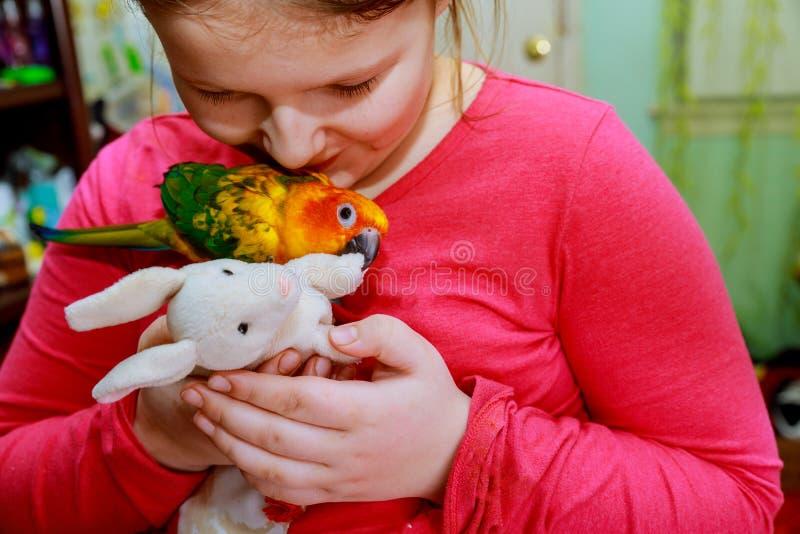 Pájaro del loro en jugar sonriente del concepto del ser humano y de la naturaleza del ambiente de la mano de la chica joven con s foto de archivo