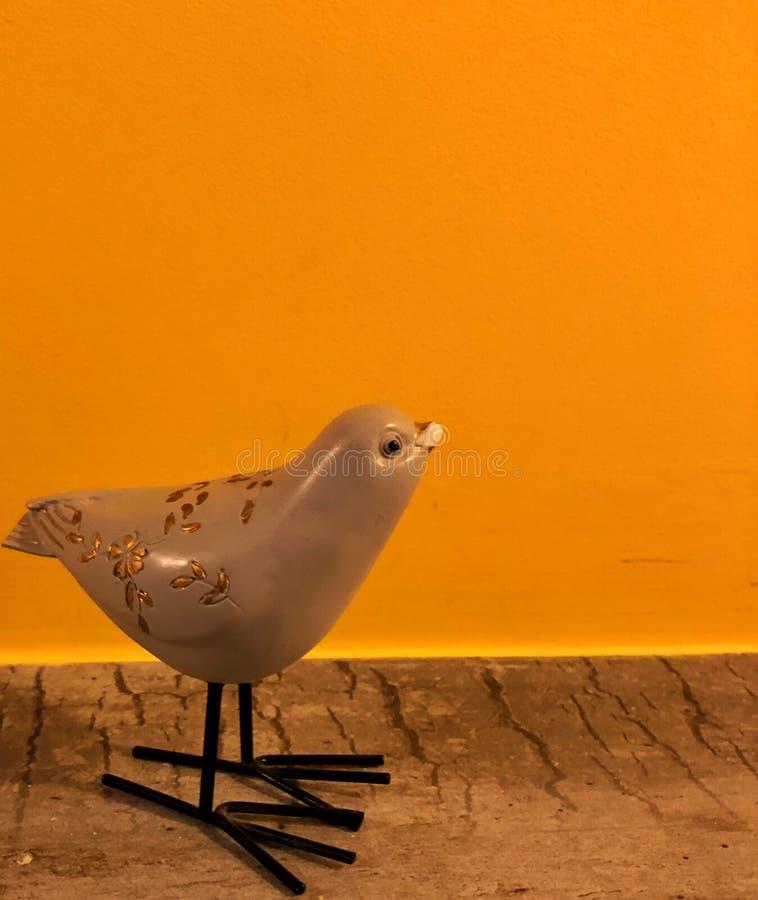 pájaro del recuerdo en un fondo amarillo anaranjado con el espacio para el texto fotografía de archivo libre de regalías