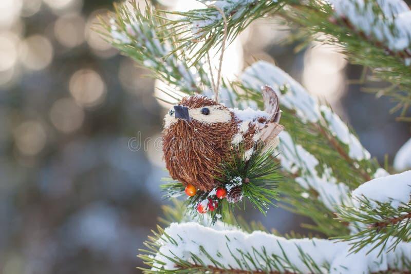 Pájaro hecho a mano del juguete del vintage de la Navidad en las ramas de un árbol nevoso imagen de archivo libre de regalías