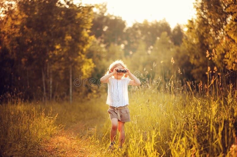 Pájaros de observación de la muchacha feliz del niño con los prismáticos en verano foto de archivo libre de regalías