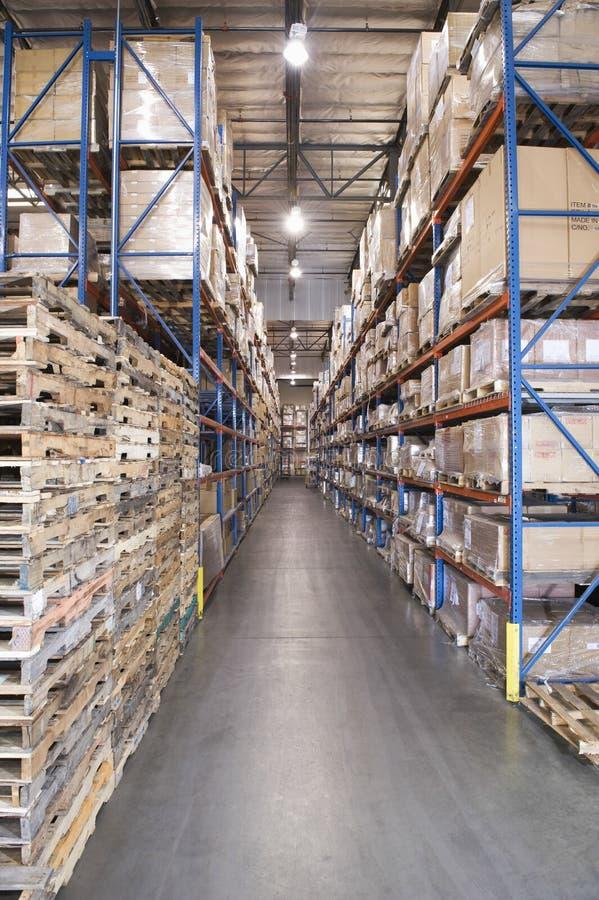 Páletes e caixas empilhadas no armazém imagem de stock