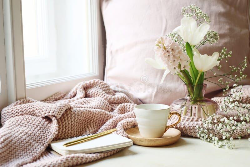 Páscoa acolhedor, cena da vida do destilador da mola Xícara de café, caderno aberto, manta feita malha cor-de-rosa na soleira Vin imagens de stock