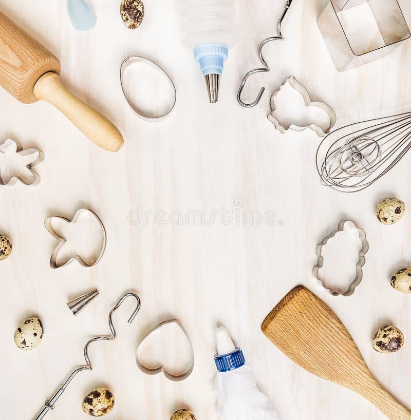 A Páscoa coze o fundo com ovos de codorniz e cortador do biscoito na tabela de madeira branca, vista superior foto de stock royalty free