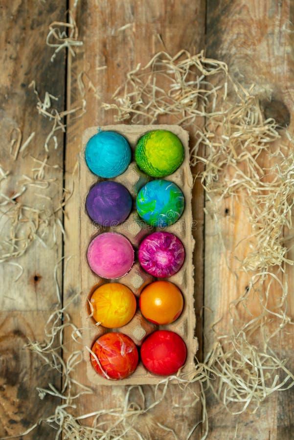 Páscoa feliz - bonita, ovos da páscoa pintados à mão brilhantes, muito coloridos em um contraste, fundo cru, natural do pla de ma imagem de stock