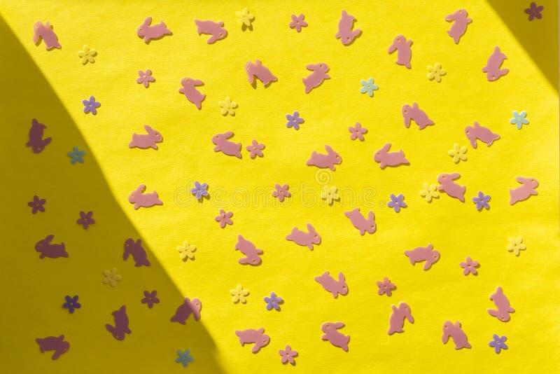 Páscoa feliz criativa - coelhos cor-de-rosa, coelhos, flores no fundo geométrico moderno colorido do papel amarelo na luz solar imagem de stock royalty free