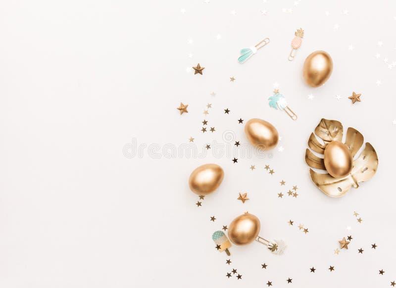 Páscoa feliz! Fundo à moda dos artigos de papelaria com os ovos do ouro no fundo branco fotos de stock royalty free