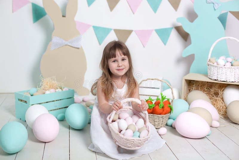 Páscoa! A menina bonita em um vestido branco coloca ovos da páscoa em uma cesta Muitos ovos da páscoa coloridos diferentes, inter fotos de stock royalty free