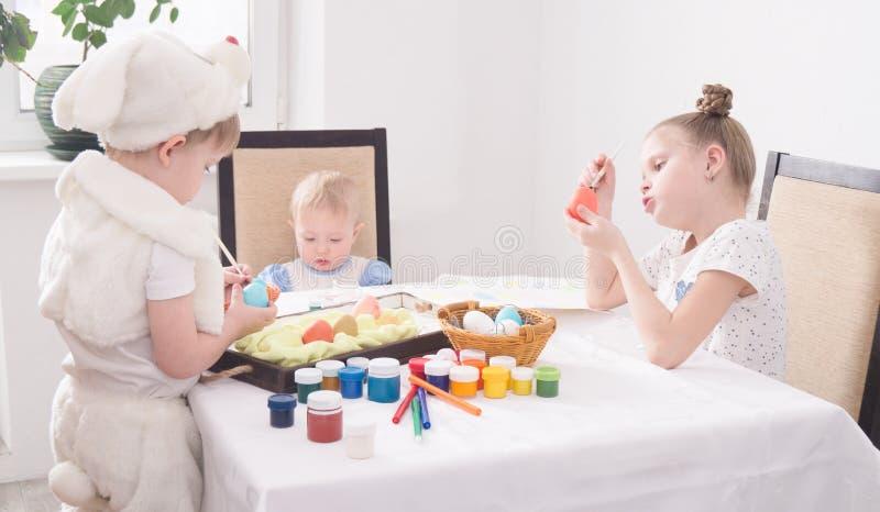 Páscoa no círculo de família: Crianças nos ovos da páscoa da pintura da tabela imagem de stock
