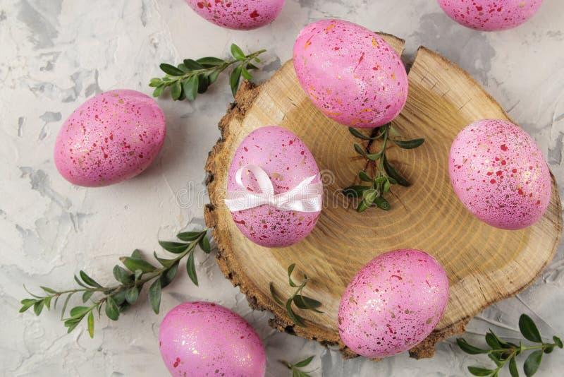Páscoa Ovos da páscoa cor-de-rosa em um suporte de madeira em um fundo do betão leve Easter feliz feriados Vista superior fotografia de stock