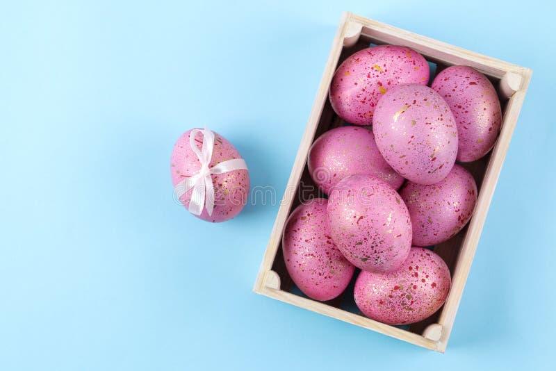 Páscoa Ovos da páscoa cor-de-rosa em uma caixa em um fundo azul na moda Easter feliz feriados Vista superior fotografia de stock royalty free