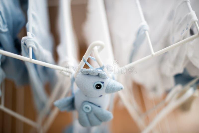 Pássaro azul do brinquedo macio perto da secagem infantil da lavanderia do bebê foto de stock royalty free