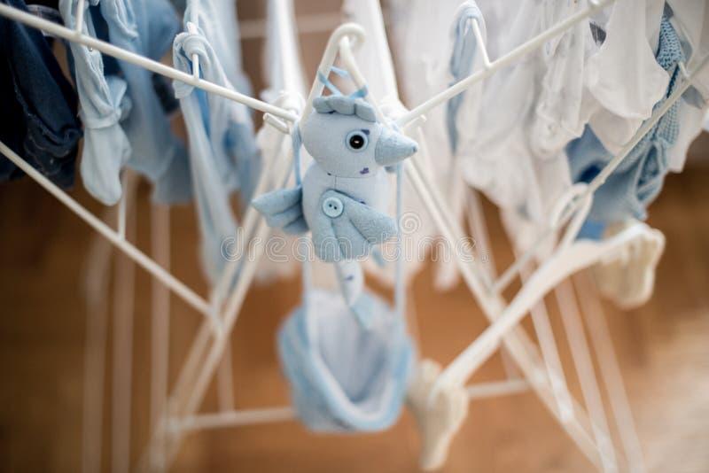 Pássaro azul do brinquedo macio perto da secagem infantil da lavanderia do bebê foto de stock