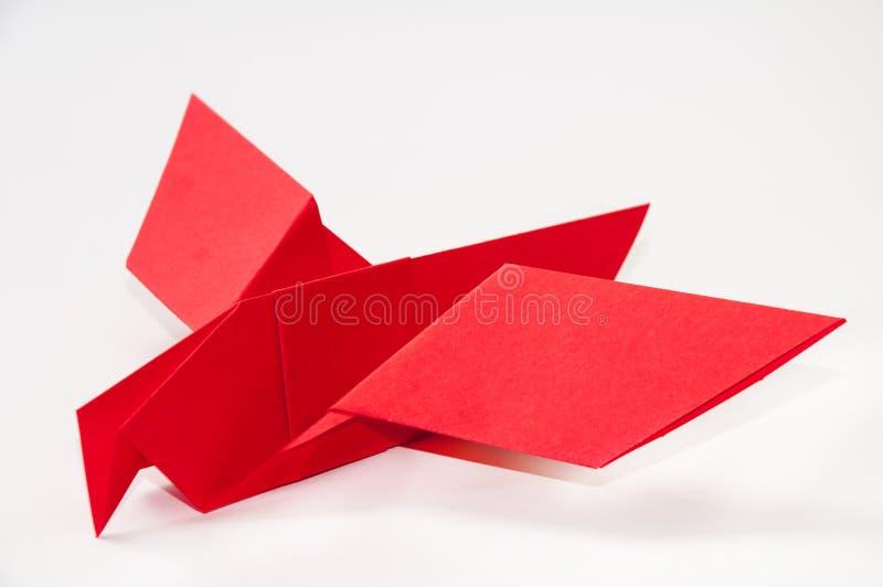 Pássaro vermelho do origâmi em um fundo branco fotografia de stock royalty free