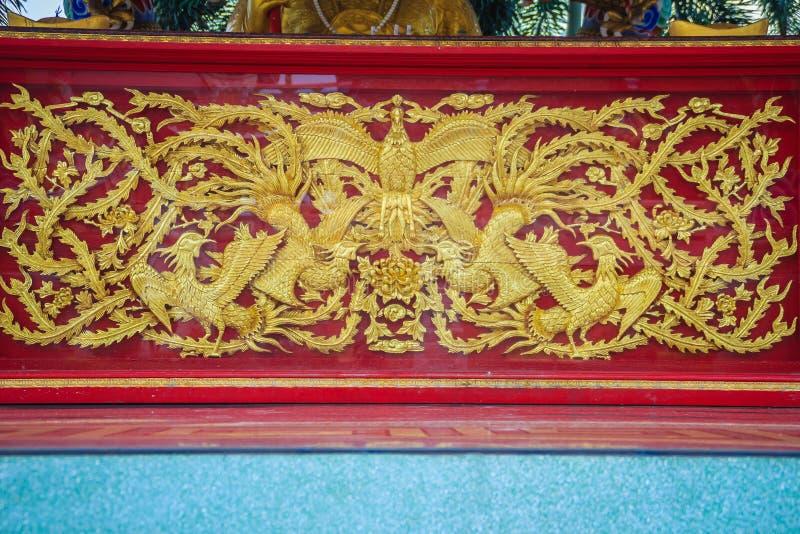 Pássaros dourados bonitos de phoenix do chinês gravados na parede vermelha fotos de stock royalty free