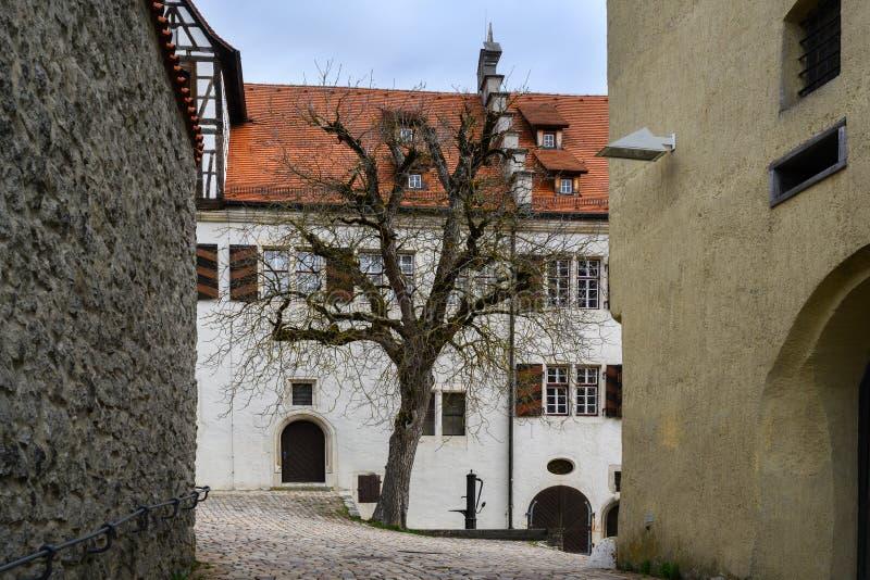 Pátio com árvore e a fonte desencapadas o castelo Hellenstein no monte de Heidenheim um der Brenz em Alemanha do sul contra a fotografia de stock