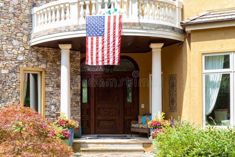 Pátio de entrada coberto da casa com a bandeira americana que pendura do balcão fotos de stock royalty free