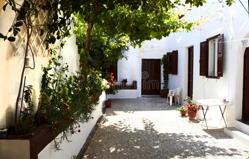Pátio estreito velho perto da casa da pedra branca com obturadores, Lindos imagens de stock royalty free