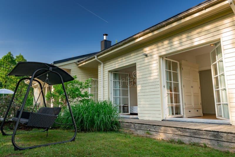Pátio perto da casa em um dia ensolarado e em um céu azul claro foto de stock royalty free