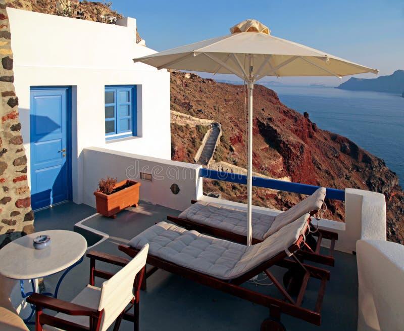 Pátio romântico com camas do sol e guarda-chuva em Santorini, Grécia fotos de stock