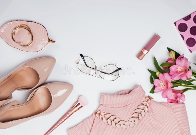 Pâle - accessoires et fleurs féminins roses sur le fond blanc images stock