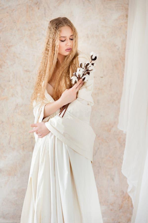 Pâlissez le portrait blond bouclé de jolie fille avec la fleur de coton photos stock