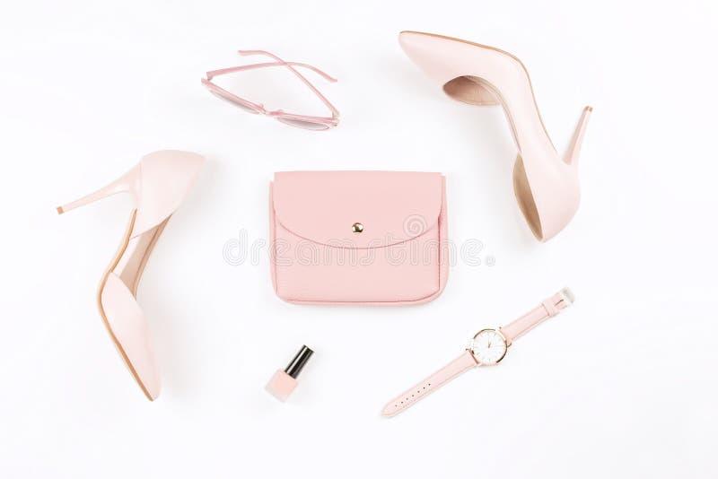 Pâlissez - les chaussures et les accessoires de mode femelles roses sur le fond blanc Configuration d'appartement de concept de b photos stock