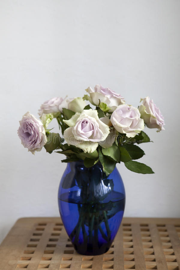 Pâlissez les roses pourpres dans le vase bleu se tenant sur la raboteuse dans l'intérieur à la maison photos stock