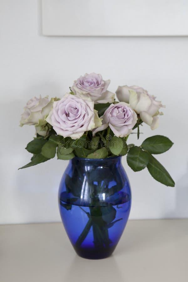 Pâlissez les roses pourpres dans le vase bleu se tenant sur la raboteuse dans l'intérieur à la maison photos libres de droits