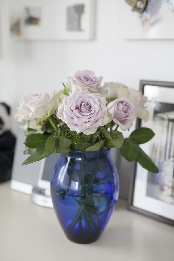 Pâlissez les roses pourpres dans le vase bleu se tenant sur la raboteuse dans l'intérieur à la maison photographie stock