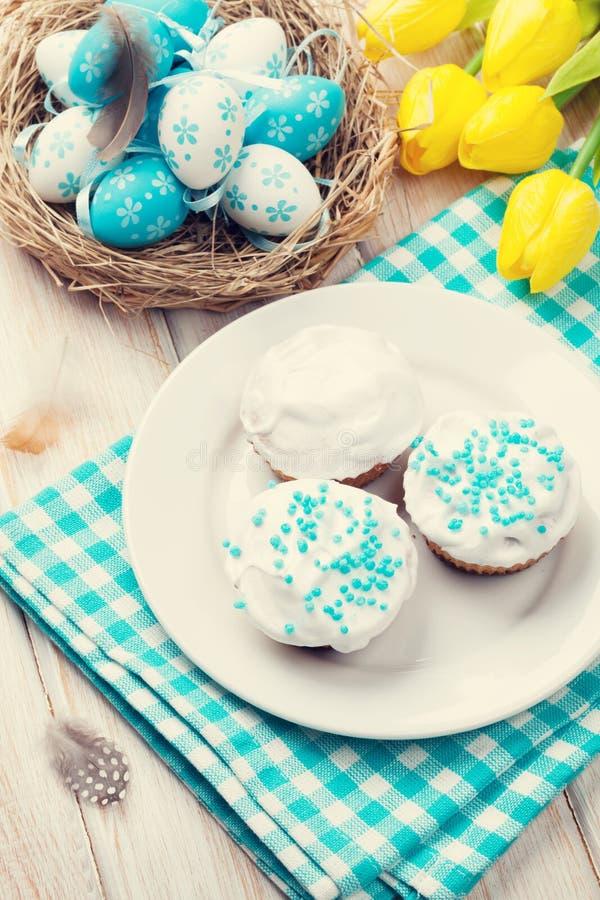 Pâques avec les tulipes jaunes, les oeufs colorés et les gâteaux traditionnels photo libre de droits