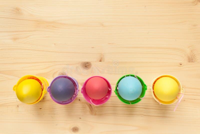Pâques a coloré des oeufs dans des seaux colorés photo stock