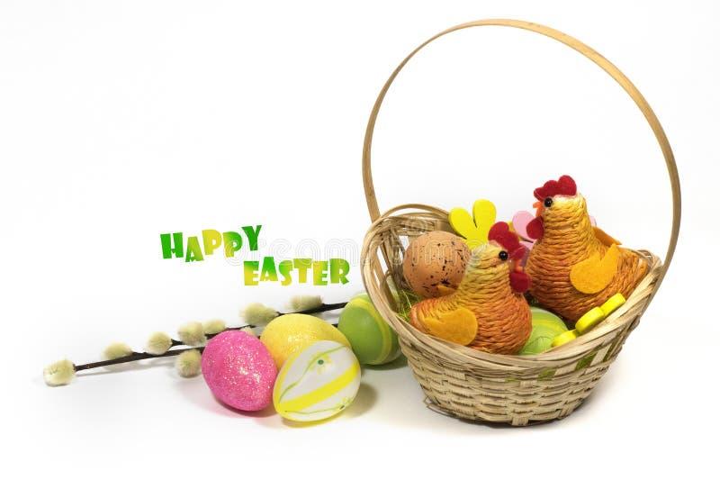 Pâques a coloré des oeufs dans un panier et un poulet décoratif de Pâques photos stock
