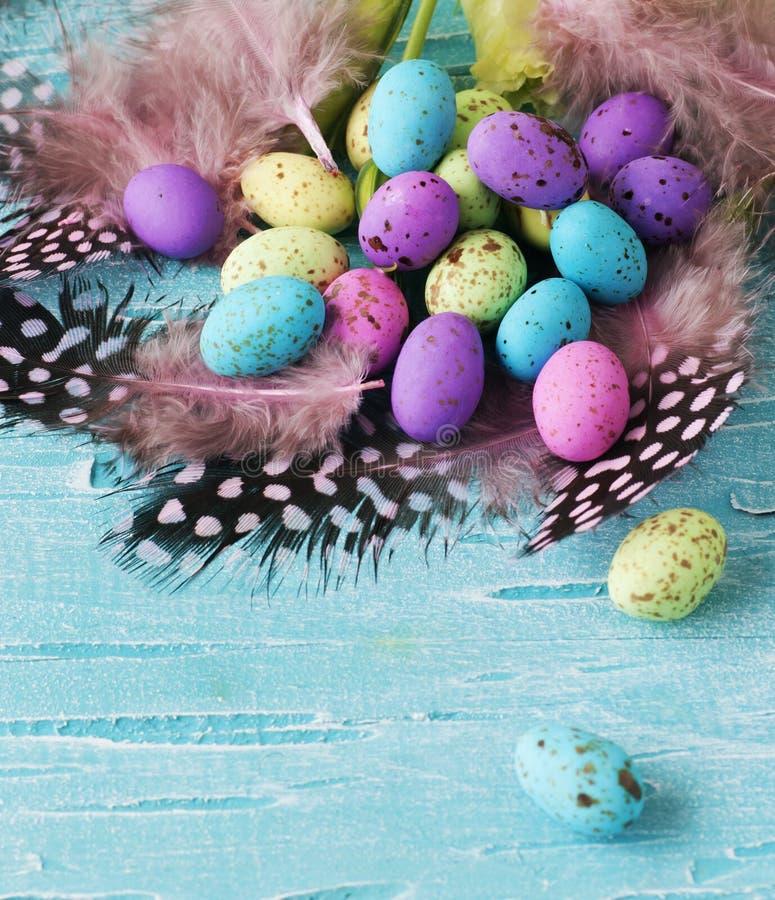 Pâques a coloré des oeufs, plumes, en bois bleu photos libres de droits