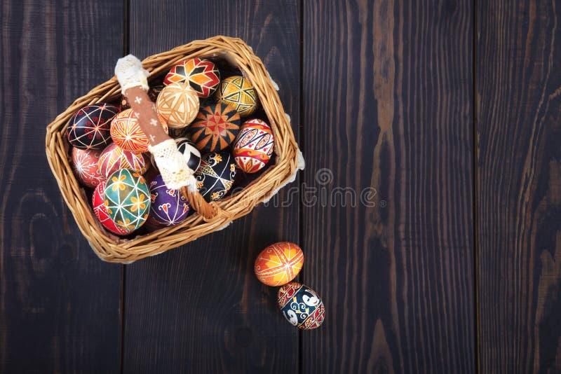 Pâques a décoré des oeufs dans le panier, sur un fond en bois images stock