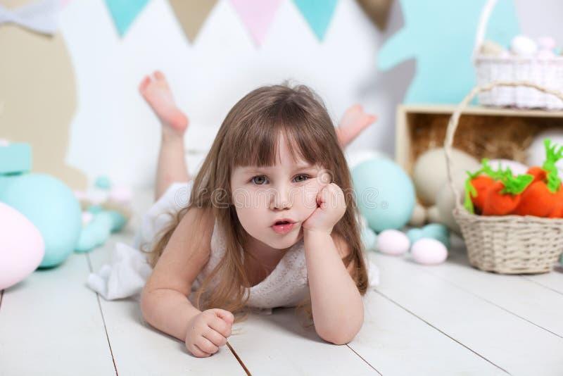 Pâques ! Portrait en gros plan d'un beau visage de petite fille Beaucoup de différents oeufs de pâques colorés, intérieur coloré  photos stock