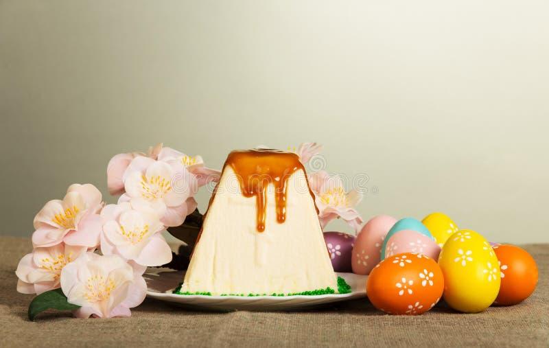 Pâques traditionnelle curds le dessert, les oeufs de pâques de couleur et les fleurs photo stock