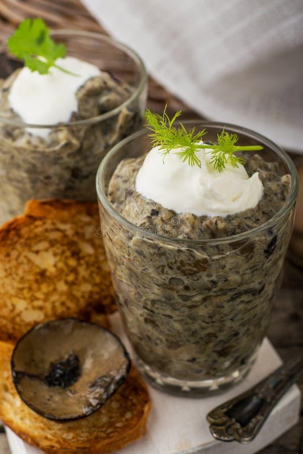 Pâté de champignon dans un pot au-dessus de fond foncé image stock