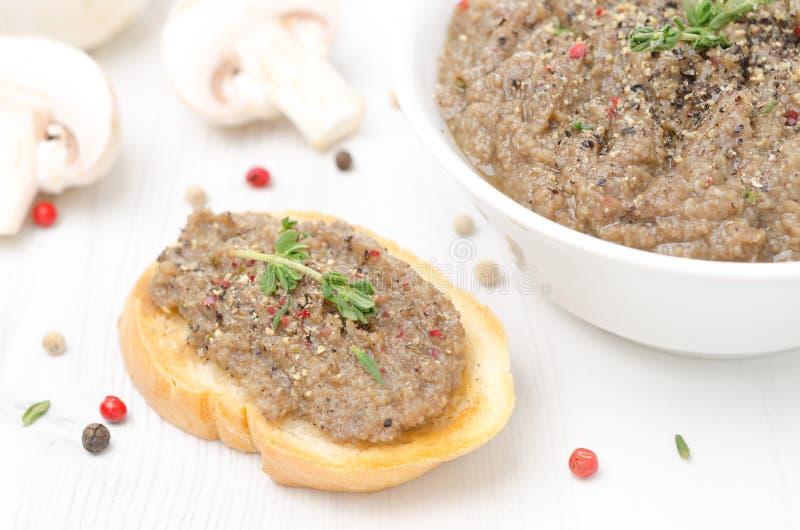Pâté de champignon sur le pain grillé et bol de pâté images stock