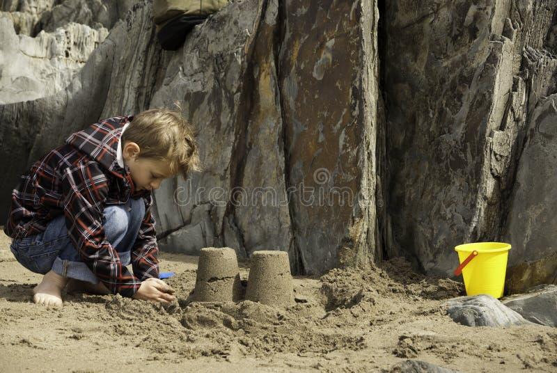 Pâté de sable de bâtiment de garçon sur Rocky Beach images libres de droits