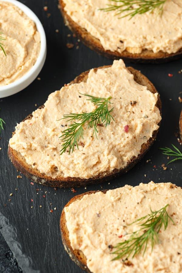 Pâté saumoné fumé fait maison frais sur le pain grillé de pain brun avec l'aneth photographie stock libre de droits