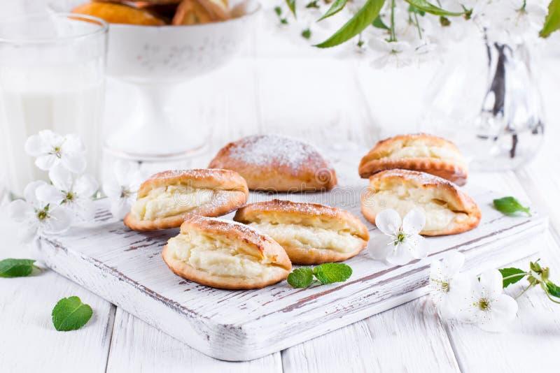 Pâtés en croûte avec le fromage blanc et le sucre en poudre sur un fond en bois clair Pâtisserie russe traditionnelle Sochnik photos libres de droits