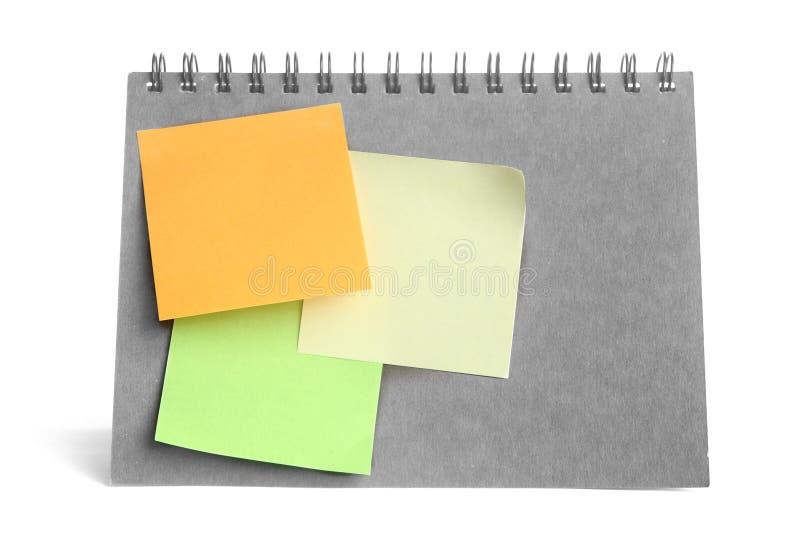 pâte colorée de post-it sur le carnet monochrome sur le fond blanc images stock