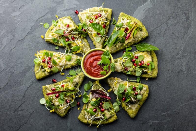 Pâte d'épinards, légumes et pizza de fromage verts, fond d'ardoise images stock