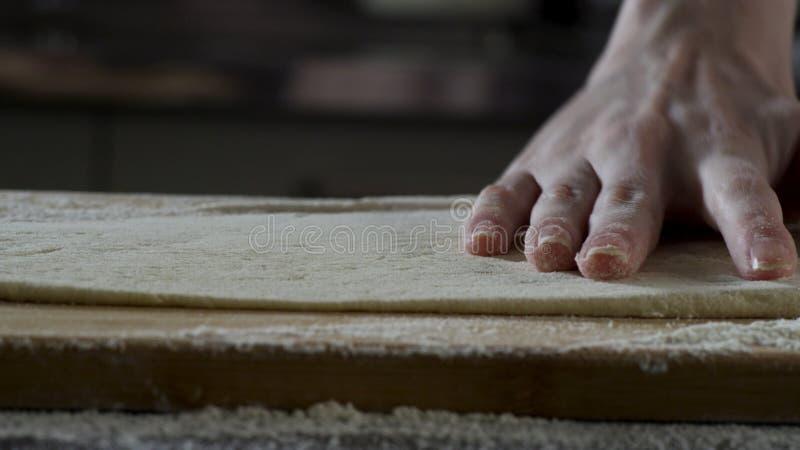 Pâte de déroulement d'homme sur la table de cuisine, fin  scène Le cuisinier roule un morceau de pâte sur la table de cuisine ave photo stock