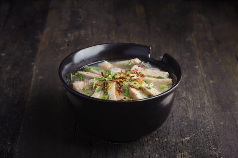 P?te de farine de riz avec l'oignon blanc, la coriandre, l'ail cuit ? la friteuse et les porks sur le dessus dans la cuvette noir photo stock