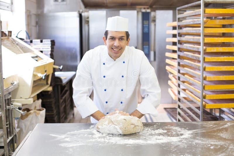 Pâte de malaxage de Baker dans la boulangerie images stock